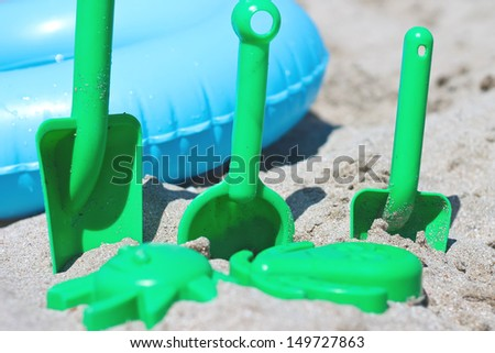 Children toys and swim ring on the sand beach - stock photo