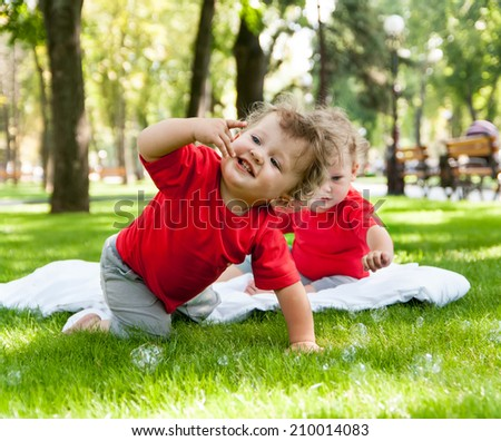 children twins play on the grass with soap bubbles - stock photo