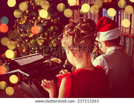 Children typing letter to Santa for Christmas presents - stock photo