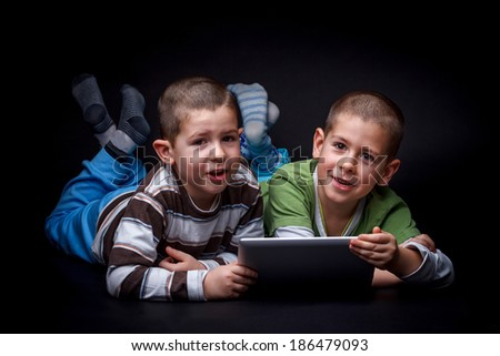 Children using electronic tablet together lying on the floor - stock photo