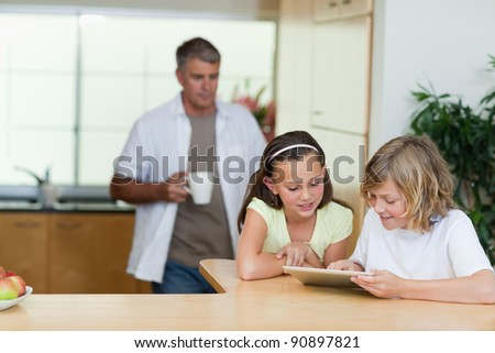 Children using tablet in the kitchen together with father behind them - stock photo