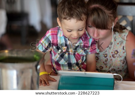Children using tablet PC in a restaurant - stock photo