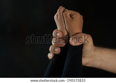 Children violence. Man's hand holding tight girl's hands - stock photo