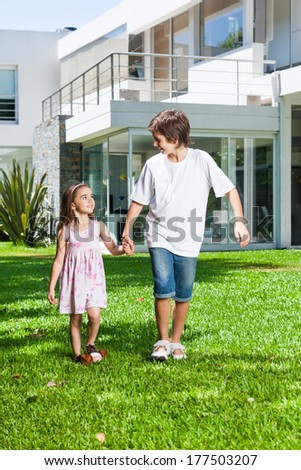 children walk outside their new house, kids smiling, sister and brother hold hands, boy and girl on green grass - stock photo