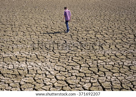 children walking on dry cracked surface - stock photo
