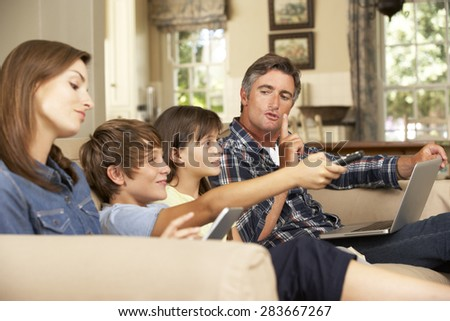 Children Watching TV Whilst Parents Use Laptop And Tablet Computer At Home - stock photo