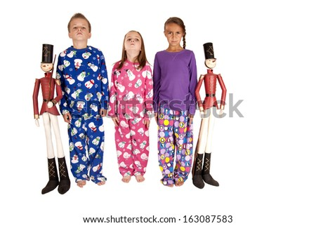 Children wearing pajamas standing at attention with soldiers stock
