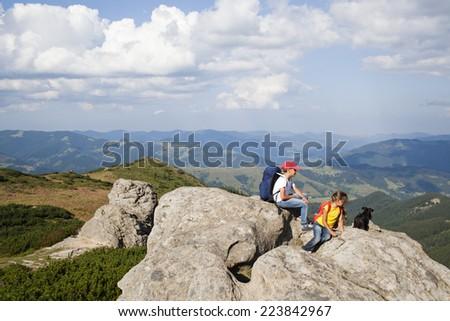 Children with dog sitting on rock above idyllic mountain peaks - stock photo