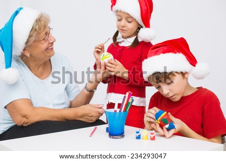 children with grandmother in santa hats preparing to Christmas - stock photo