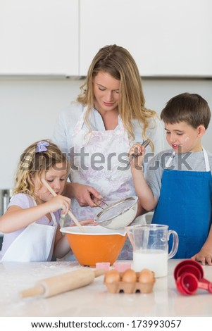 Children with mother baking cookies at counter top in kitchen - stock photo