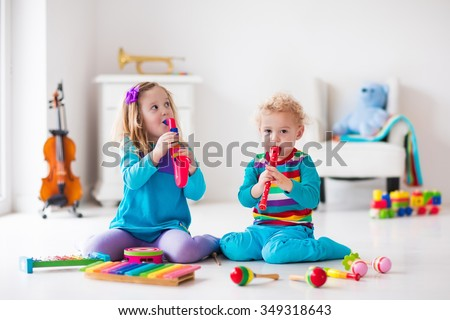 Children with music instruments. Musical education for kids. Colorful wooden art toys. Little girl and boy play music. Kid with xylophone, guitar, flute, violin. Early development for toddler and baby - stock photo