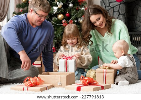 Children with parents in the morning opening presents under the Christmas tree - stock photo