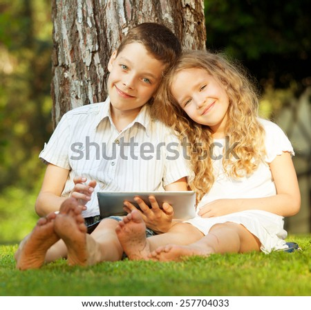 Children with tablet computer outdoors. Girl and boy playing at pc  - stock photo