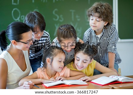 Children with teacher in classroom - stock photo