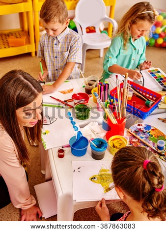 Children with teacher woman learn painting on color paper in  art class kindergarten . Top view. - stock photo