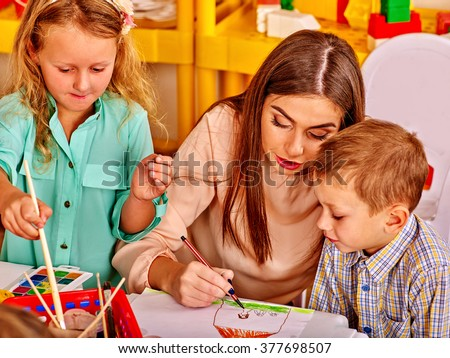 Children with teacher woman painting on drawing lesson  in  kindergarten .  - stock photo