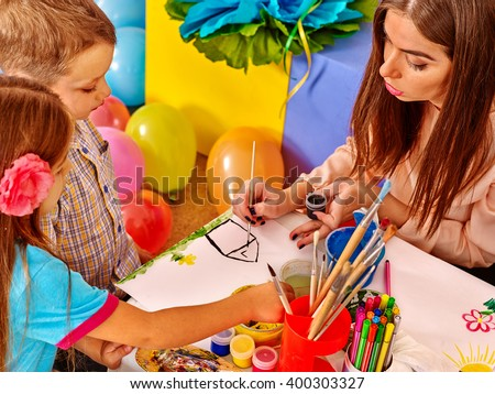 Children with teacher woman painting on paper at table  in  kindergarten . Balloons on floor. - stock photo