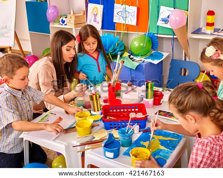 Children with teacher woman painting on paper at table  in  kindergarten . Children learn painting in start school. - stock photo