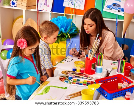Children with teacher woman painting on paper at table  in  kindergarten . Group people. - stock photo