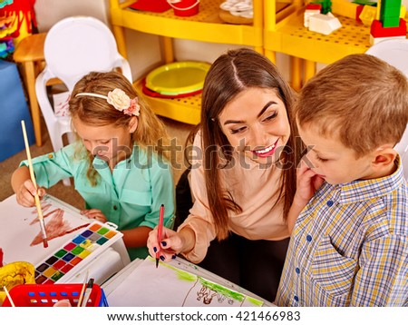 Children with teacher woman painting on paper at table  in  kindergarten . Learning children in start school. - stock photo