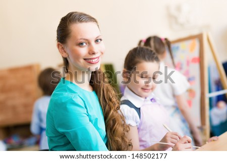 children with the teacher engaged in painting at an art school - stock photo