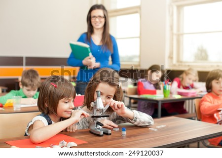 Children working with microscope on creative workshop on biology class. Young teacher is casual clothed - stock photo