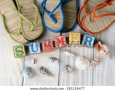 Childrens blocks spelling out Summer on rustic wooden boards The word is surrounded by sea shells, and flip-flop style sandals. Horizontal format. - stock photo