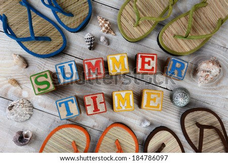 Childrens Blocks Spelling Out Summer Time on a rustic wooden boardwalk. The words are surrounded buy sea shells and flip-flop style sandals. Horizontal format. - stock photo