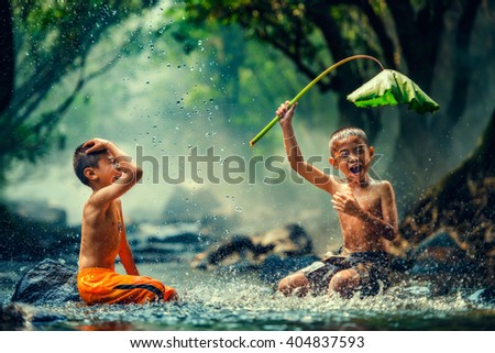 Childrens playing in the river - stock photo