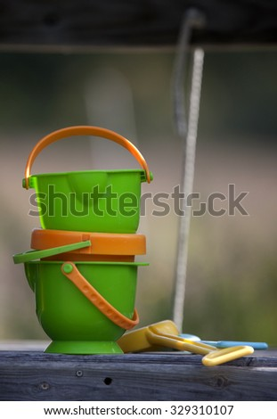Childrens sandbox pails blurry backgroundgreen and yellow - stock photo