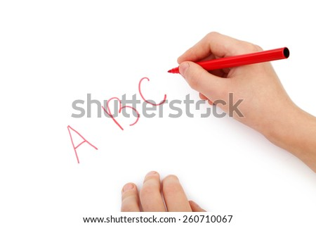 Childs hands writing letters on white paper - stock photo