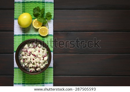 Chilean Ceviche made of Southern Ray's bream fish (lat. Brama Australis, Spanish Reineta), onion, garlic and cilantro marinated in lemon juice. Photographed overhead on dark wood with natural light. - stock photo