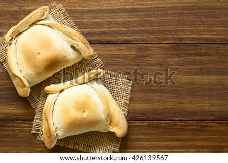 Chilean Empanada, a baked pastry stuffed with meat, photographed overhead on dark wood with natural light - stock photo