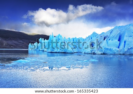 Chilean Patagonia. National Park Torres del Paine. Lake and Glacier Grey. A sharp wind and the cold sun over blue ice. Grey glacier moves down the water of the lake - stock photo