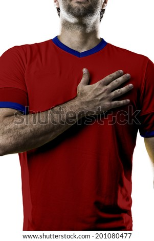 Chilean soccer player, listening to the national anthem with his hand on his chest. On a white background. - stock photo