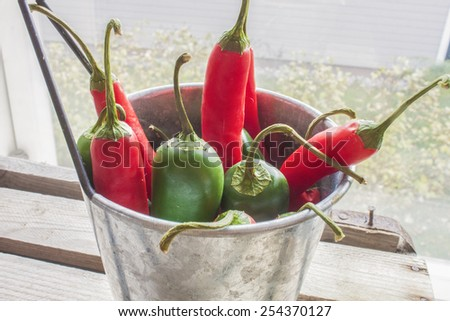 Chili and jalapeno, in a aluminium bowl, on wooden ground - stock photo