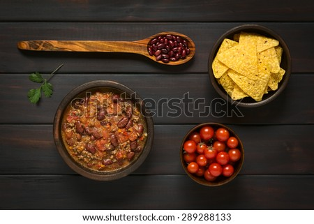 Chili con carne and tortilla chips with ingredients dried kidney beans and cherry tomatoes, photographed overhead on dark wood with natural light - stock photo
