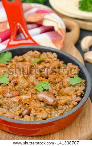 chili con carne in a cast iron skillet on a wooden board vertical - stock photo