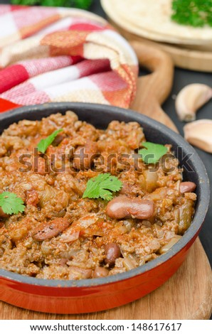 chili con carne in a cast iron skillet on a wooden board vertical closeup - stock photo