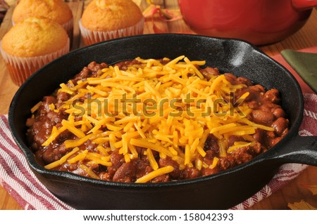 Chili con carne in a cast iron skillet topped with cheddar cheese - stock photo