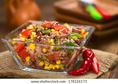 Chili con carne salad made of mincemeat, kidney beans, green bell pepper, tomato, sweet corn and red onions served in glass bowl (Selective Focus, Focus in the middle of the salad) - stock photo