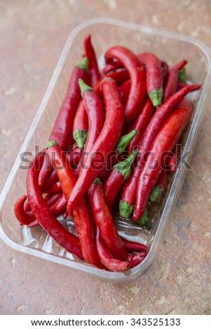 Chili hot peppers on wood background - stock photo
