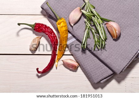 Chili pepper and flavoring herbs isolated on wooden background - stock photo