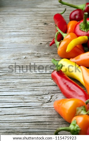 Chili peppers and wood texture background - stock photo