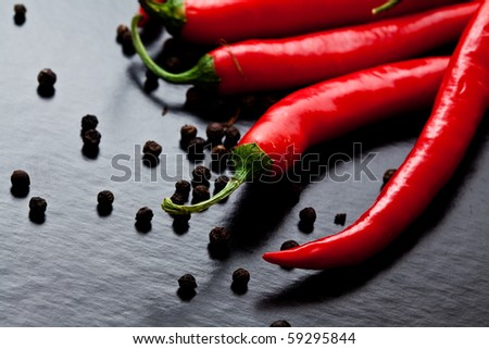 chili peppers with black pepper on dark textured background - stock photo