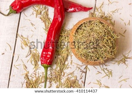 Chili  red pepper and rosemary on a white table. - stock photo