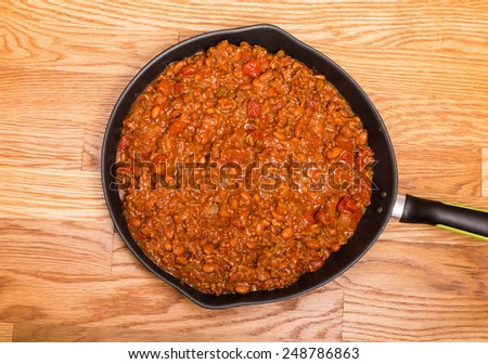 Chili with meat and beans in a black iron skillet on a wood table - stock photo