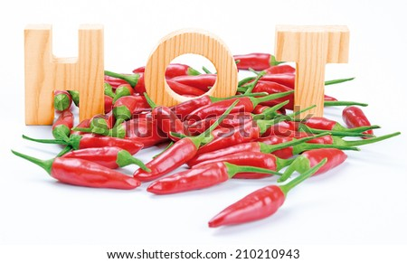 Chilies And HOT Wooden Letters - Red fresh chilies with three wooden letters writing the word HOT. - stock photo