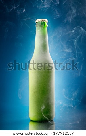 Chilled beer bottle on blue background - stock photo