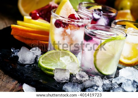 Chilled soft drinks with ice, citrus fruits and berries, black background, selective focus - stock photo